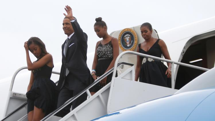 U.S. President Barack Obama waves as he and his family arrive aboard Air Force One at Westchester County Airport in New York