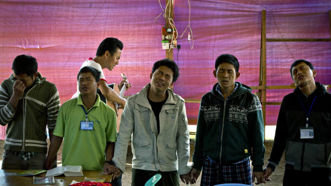 In this photo taken on Feb 12, 2013, Kun Htoi Shawong, background plays the guitar and sings as residents in tears join hands during a religious healing session at the Kachin Baptist Convention's rehabilitation camp in Myitkyina, the provincial capital of Kachin state, Myanmar. Myitkyina is known for having one of the highest concentrations of drug addicts in the world. The Kachin Baptist Convention, an evangelical group with over 300 churches in the state, says nearly 80 percent of ethnic Kachin youth are addicts. Their drug of choice is heroin. In the shadow of war, even drug abuse becomes politicized. Gryung Heang, the pastor of the camp church, says the government is willfully turning a blind eye to drug abuse among the Kachin because it wants to decimate young potential fighters. Officials say such views are absurd.(AP Photo/Gemunu Amarasinghe)