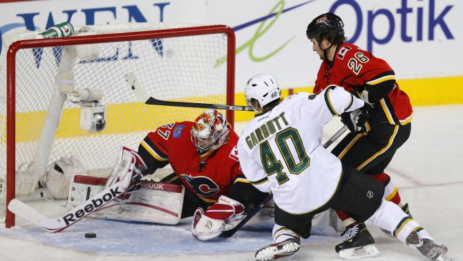 Calgary Flames Irving makes a save on Dallas Stars' Garbutt while Flames' Wideman tries to take him out of the play during their NHL hockey game in Calgary.
