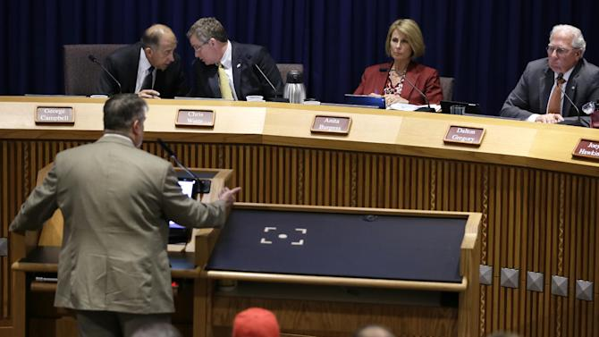 Council member George Campbell, left rear, talks with Mayor Chris Watts as council persons Anita Burgess and Dalton Gregory right, listen to Former Texas Railroad Commission executive director John Tintara, at podium, speak at a public hearing at City Hall, Tuesday, July 15, 2014, in Denton, Texas. Current and former Texas officials have warned a North Texas city that it lacks the authority to enact a ban it's considering on hydraulic fracturing. (AP Photo/Tony Gutierrez)