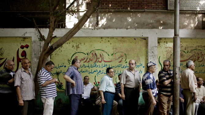 Egyptian men line up to vote at a polling station in the Shobra neighborhood of Cairo, Egypt on Sunday, June 17, 2012. Egyptians are choosing on Sunday between a conservative Islamist and Hosni Mubarak's ex-prime minister in the second day of a presidential runoff that has been overshadowed by questions on whether the ruling military will transfer power to civilian authority by July 1 as promised. (AP Photo/Pete Muller)