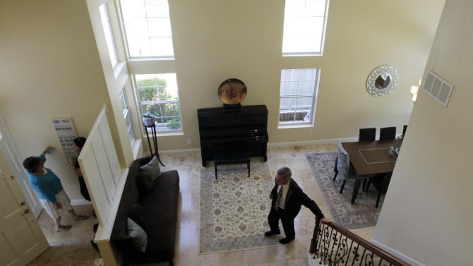 In this June 13, 2012, photo, real estate agent Jim Klinge, right, hosts an open house in San Diego. Mortgage buyer Freddie Mac said Thursday, June 14, 2012, that average rates on fixed mortgages rose this week, the first increase in seven weeks, but they remain near historic lows, boosting prospects for home sales this year. (AP Photo/Gregory Bull)