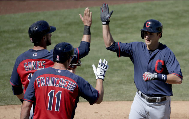 Cleveland Indians's Lonnie Chisenhall, right, celebrates his two-run home run with Yan Gomes, left, and Jeff Francoeur during the fourth inning of a spring exhibition baseball game against the Ari