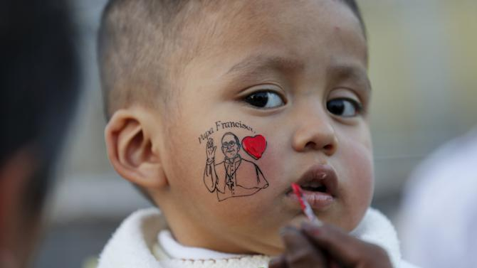 A baby gets a face paint of Pope Francis in Mexico City