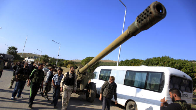 Syrian fighters walk past an artillery canon they took after storming a military base in Aleppo, Monday, Nov. 19, 2012. (AP Photo/ Khalil Hamra)