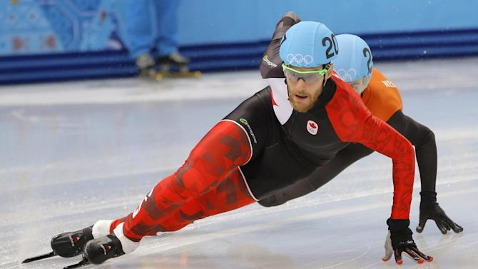 Olivier Jean of Canada, front, and Sjinkie Knegt of Netherlands compete in a men's 1000m short track speedskating heat at the Iceberg Skating Palace during the 2014 Winter Olympics, Thursday, Feb. 13, 2014, in Sochi, Russia