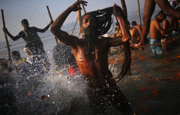 "A ""Naga"" sadhu or Hindu naked holy man takes a dip at ""Sangam,"" the confluence of Hindu holy rivers Ganges, Yamuna and the mythical Saraswati, during the Maha Kumbh festival at Allahabad, India, Sunda"