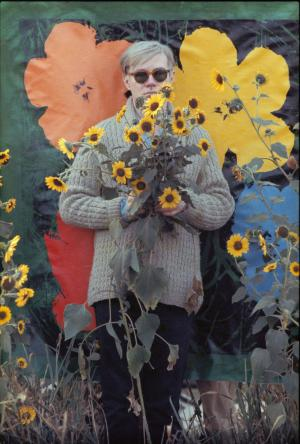 "In this 1964 photo provided by Allen Cooper Enterprises, artist Andy Warhol stands in a field of Black-Eyed Susans in New York. The image will be featured in an exhibit entitled: ""Before They Were Famous: Behind the Lens of William John Kennedy,"" which opens on April 19th at the Site/109 gallery in New York. (AP Photo/William John Kennedy via Allen Cooper Enterprises)"