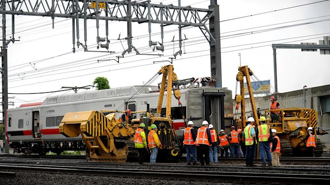 A derailed Metro-North rail car is hoisted back on to the tracks in Bridgeport. Conn. on Sunday, May 19, 2013. Crews will spend days rebuilding 2,000 feet of track, overhead wires and signals following the collision between two trains Friday evening that injured 72 people, Metro-North President Howard Permut said Sunday. (AP Photo/The Connecticut Post,Brian A. Pounds ) MANDATORY CREDIT
