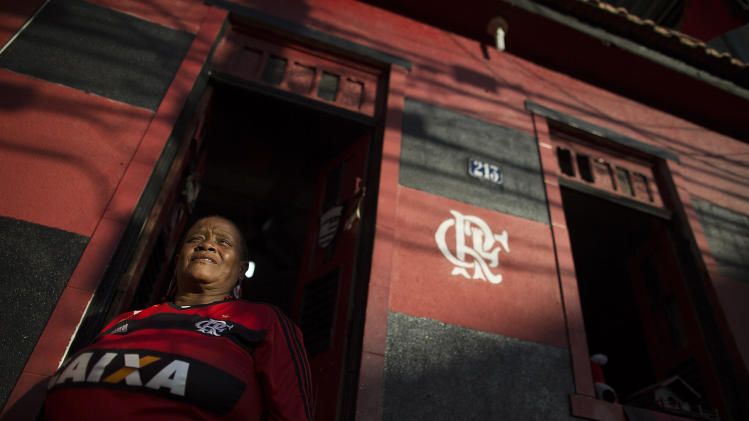 In this April 28, 2014 photo, Maria Boreth de Souza, alias Zica, poses for a portrait in her Flamengo club jersey in the doorway of her home painted in her team's colors of red and black in the Olaria neighborhood of Rio de Janeiro, Brazil. The 63-year-old is one of the most die-hard and the best known fans of the iconic team who has over the years become an icon in her own right. Her nickname Zica is honor of former Brazilian soccer great Zico. (AP Photo/Leo Correa)