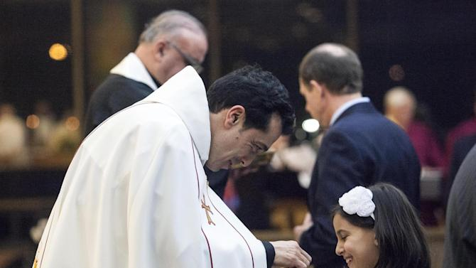 Wissam Akiki, who is married, left, serves his daughter, Perla, communion after being ordained during a ceremony at St. Raymond's Maronite Cathedral Thursday, Feb. 27, 2014, in St. Louis. Akiki is the first married priest to be ordained by the Maronite Catholic Church in the United States in nearly a century. (AP Photo/Erin Stubblefield)