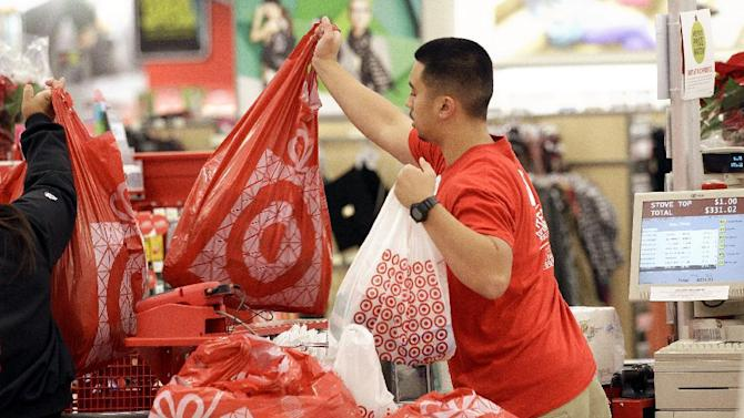 FILE - In this Nov. 23, 2012 file photo, a Target employee hands bags to a customer at the register at a Target store in Colma, Calif. Target's fiscal fourth-quarter net income dipped 2 percent as it dealt with intense competition during the crucial holiday season. But its adjusted results beat analysts' estimates and it forecast first-quarter earnings above Wall Street's view. (AP Photo/Jeff Chiu, File)