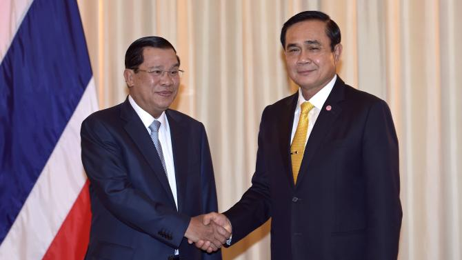 Thailand's Prime Minister Prayuth Chan-ocha shakes hand with Cambodia's Prime Minister Hun Sen at the Government House in Bangkok