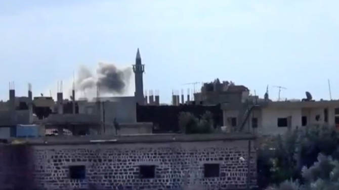 In this image taken from video obtained from the Shaam News Network, which has been authenticated based on its contents and other AP reporting, smoke rises from buildings due to heavy shelling in Daraa, Syria, on Thursday, Jan. 24, 2013. (AP Photo/Shaam News Network via AP video)