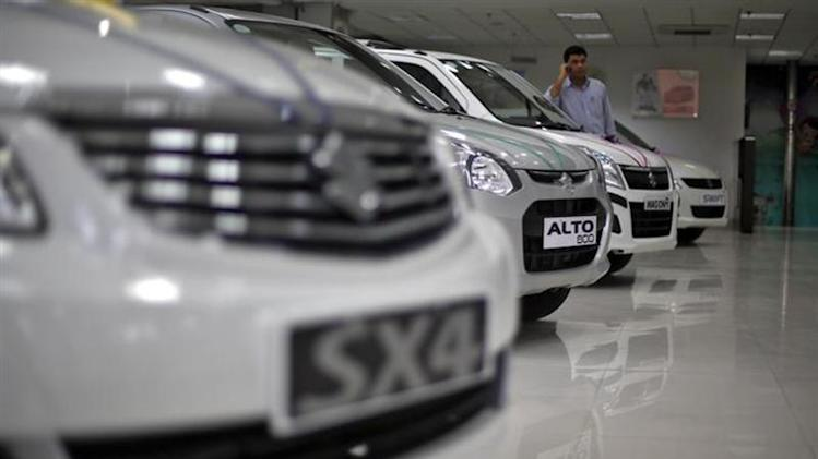 A sales executive speaks on his mobile phone as he stands in between Maruti Suzuki cars inside a showroom in New Delhi April 9, 2013. REUTERS/Adnan Abidi/Files