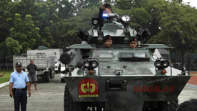 An Armored Personnel Carrier of the Philippine National Police runs over piles of pirated DVDs during ceremonial destruction of counterfeit goods seized in raids recently at parade grounds of the police headquarters at suburban Quezon city, northeast of Manila, Thursday June 30, 2011. The ceremonial destruction of pirated DVDs and other counterfeit goods was done to coincide with the global celebration and awareness campaign known as World Anti-Counterfeiting Day. (AP Photo/Bullit Marquez)