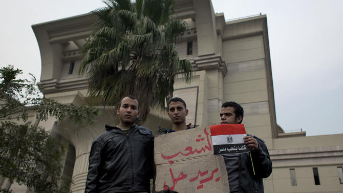 "Supporters of Egyptian President Mohammed Morsi hold a placard with Arabic that reads, ""the people want to solve the constitution,"" outside Egypt's top court in Cairo, Sunday, Dec. 2, 2012. Egypt's top court announced on Sunday the suspension of its work indefinitely to protest ""psychological and physical pressures,"" saying its judges could not enter its Nile-side building because of the Islamist president's supporters gathered outside. (AP Photo/Nasser Nasser)"