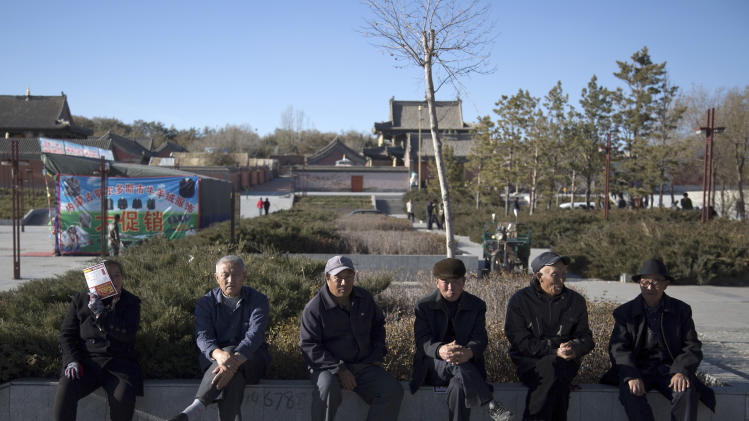 In this photo taken on Thursday, Oct. 25, 2012, a woman covers her face with a leaflet as she sits with a group of elderly men near a temple in Xilinhot in northern China's Inner Mongolia. In the small town where sheep and cattle easily outnumber humans, a deputy chief paid three times an average urban resident's annual salary to become its police chief. Buying and selling office is so rampant in China that it has eroded public trust in officialdom, undermining the ruling Communist Party's image as an institute that promotes the competent, not the connected. Even though Chinese leaders have vowed to eradicate the practice, it has showed no sign of abatement. (AP Photo/Andy Wong)