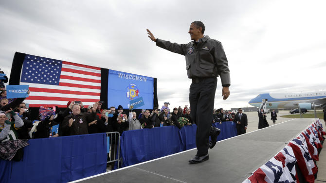 President Barack Obama waves to supporters as he walks on stage for a campaign event at Austin Straubel International Airport in Green Bay, Wis.,Thursday, Nov. 1, 2012. Obama resumed his presidential campaign with travel to key background states of Wisconsin, Colorado, Nevada and Ohio today. (AP Photo/Pablo Martinez Monsivais)
