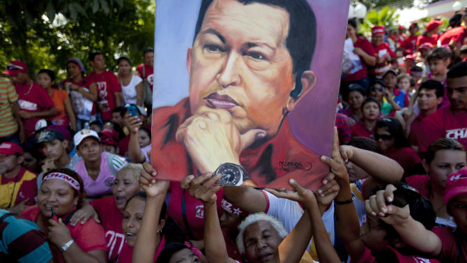 Supporters of Venezuela's President Hugo Chavez hold up an image of him during a campaign caravan from Barinas to Caracas, in Sabaneta, Venezuela, Monday, Oct. 1, 2012. Venezuela's presidential election is scheduled for Oct. 7. (AP Photo/Rodrigo Abd)