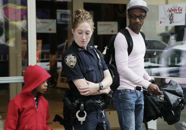 "A New York City police officer watches as movie patrons arrive for a screening of ""The Dark Knight Rises,"" Friday, July 20, 2012 in New York. A gunman in a gas mask barged into a crowded Denver-area theater during a midnight premiere of the Batman movie on Friday, hurled a gas canister and then opened fire, killing 12 people and injuring at least 50 others in one of the deadliest mass shootings in recent U.S. history. NYPD commissioner Ray Kelly said the department was providing the extra security at theaters ""as a precaution against copycats and to raise the comfort levels among movie patrons."" (AP Photo/Mark Lennihan)"