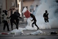 Bahraini protesters run for cover from tear gas during a demonstration to mark the second anniversary of the uprising in the village of Sanabis, west of the capital Manama on February 14, 2013. Bahrain's opposition called a rally near Manama marking the second anniversary of a Shiite-led uprising against the kingdom's Sunni rulers, a day after two people died when protests turned violent
