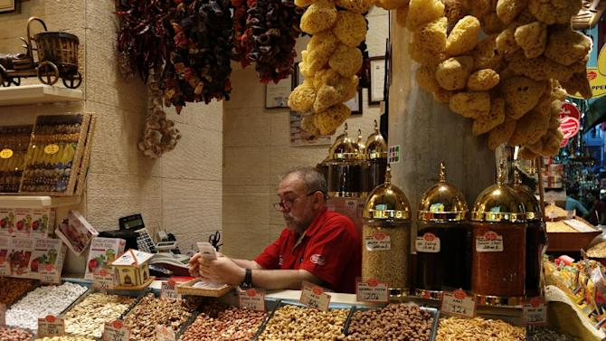 "A man sits in his shop in the 17th century Spice Market, or the Egyptian Bazaar, with stalls beautifully displaying spices, dried fruit, nuts, apple tea, essential oils, and ""Turkish Delight"" candy in Istanbul, Turkey, Tuesday, Oct. 29, 2013. Last summer, Istanbul's Taksim Square was the scene of violent confrontations between police and protesters. But protests have faded, and contrary to some lingering perceptions, it's quite calm now _ except for the normal hustle and bustle found in this vibrant city. And it's as safe for tourists as it ever was. Istanbul is a thoroughly modern place, but it traces its roots back to 660 B.C. It's the former seat of the opulent Byzantine and Ottoman empires and is divided into European and Asian sides by the Bosporus Strait, offering a wealth of history and stunning scenery.(AP Photo)"