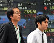 Businessmen walk past a share price display board in Tokyo earlier this month. Asian markets were mixed on Wednesday, with attention turning to a speech by US Federal Reserve chief Ben Bernanke later in the week as dealers look for an indication of any stimulus by the central bank