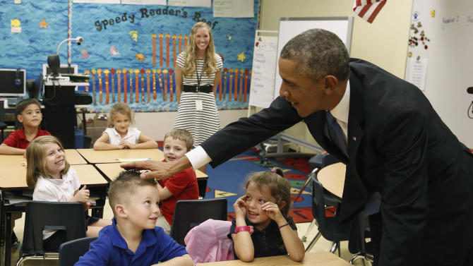 U.S. President Barack Obama touches the spiked hair style of a child while visiting the Clarence Tinker elementary school children while at MacDill Air Force Base in Tampa