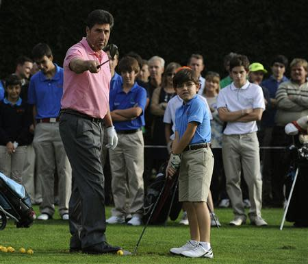 Spanish golfer Jose Maria Olazabal instructs a child during a golf clinic in La Barganiza