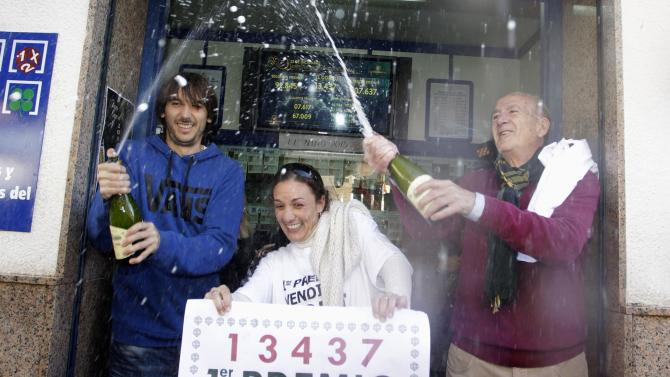 """Lottery seller Raquel Carrasco holds a sign with the winning number of Spain's Christmas Lottery """"El Gordo"""", in La Eliana"""