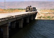In this photo taken during a government-organised visit for media, a Syrian army tank and military truck, are seen cross the bridge of al-Assi river, near the town of Jisr al-Shughour, north of Damascus, Syria,on Friday June 10, 2011. Elite Syrian forces moved swiftly through the country's restive north on Friday, raining tank shells on rebellious towns, torching farmland and shooting protesters who tried to tear down a poster of President Bashar Assad, activists and refugees said.(AP Photo/Bassem Tellawi)