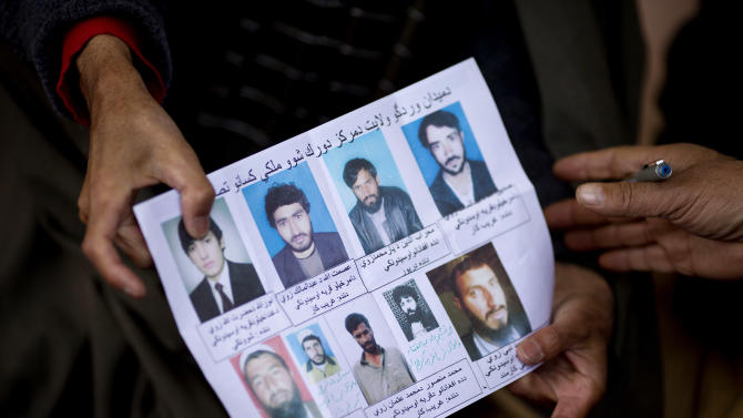 Afghan villagers show a paper with pictures of relatives held in U.S. Special Forces custody in Maidan Shahr, Wardak province, Afghanistan, Sunday, March 10, 2013. Afghan President Hamid Karzai, infuriated by villager reports of forced detentions and mass arrests, gave U.S. Special Forces two weeks to vacate Wardak province, located barely 30 kilometers (24 miles) from the Afghan capital of Kabul. The deadline for their withdrawal expired midnight Sunday, March 10, 2013. (AP Photo/Anja Niedringhaus)