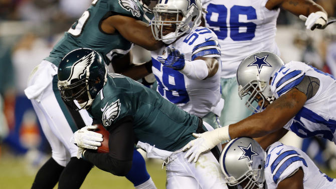 Philadelphia Eagles quarterback Michael Vick, left, is tackled by Dallas Cowboys inside linebacker Ernie Sims, defensive end Jason Hatcher and outside linebacker DeMarcus Ware in the first half of an NFL football game, Sunday, Nov. 11, 2012, in Philadelphia. (AP Photo/Julio Cortez)