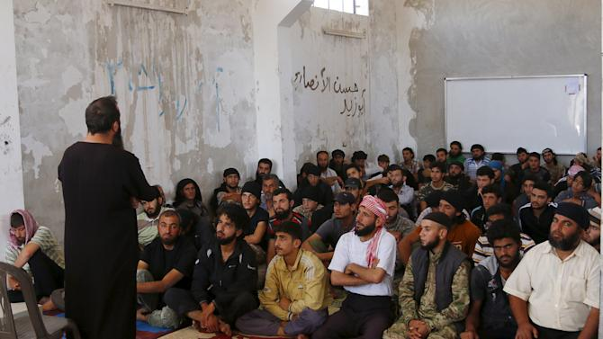 Rebel fighters from the Ahrar al-Sham Movement take Islamic and Koran lessons inside a camp, during the holy month of Ramadan in Idlib countryside, Syria