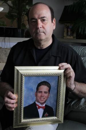 In this March 22, 2012 photo, Arthur Baselice Jr., poses for a photograph with a picture of his son Arthur Baselice III, in Mantua, N.J. Arthur III overdosed in 2006, after his 2004 civil suit accusing a Philadelphia priest of abuse was thrown out. (AP Photo/Alex Brandon)