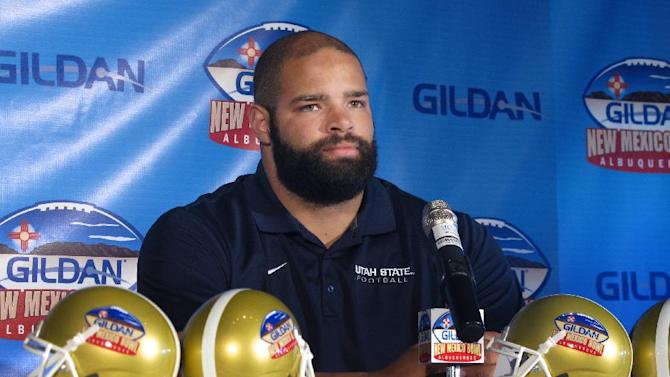 Utah State's Kevin Whimpey talks to reporters Friday, Dec. 19, 2014, in Albuquerque, N.M. Utah State is set to square off with UTEP and its run-heavy offense to launch the college football postseason Saturday at the New Mexico Bowl. (AP Photo/Russell Contreras)