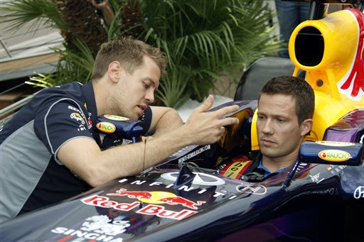 Red Bull driver Sebastian Vettel of Germany, left,  gestures as Volkswagen rally French driver Sbastien Ogier sits on a Red Bull F1 car, at the Monaco racetrack, in Monaco, Wednesday, May 22, 2013. Th