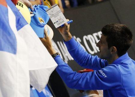 Novak Djokovic of Serbia signs autographs after defeating Milos Raonic of Canada in their men's singles quarter-final match at the Australian Open 2015 tennis tournament in Melbourne