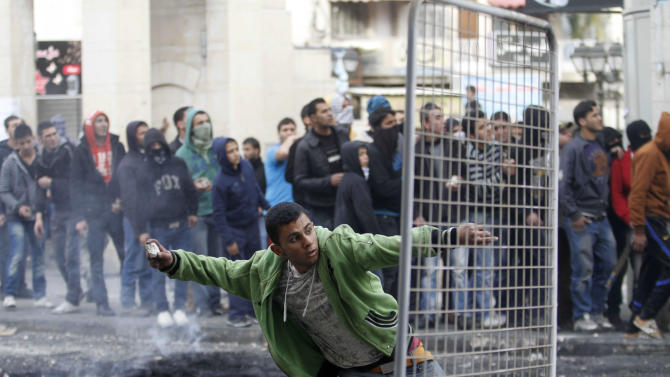 A Palestinian man throws a stone towards Israeli soldiers after the funeral of Arafat Jaradat in the West Bank of Hebron, Monday, Feb. 25, 2013. Thousands have attended the funeral procession of a 30-year-old Palestinian man who died under disputed circumstances in Israeli custody. Palestinian officials say autopsy results show Jaradat was tortured by Israeli interrogators, while Israeli officials say there's no conclusive cause of death yet and that more tests are needed.(AP Photo/Nasser Shiyoukhi)