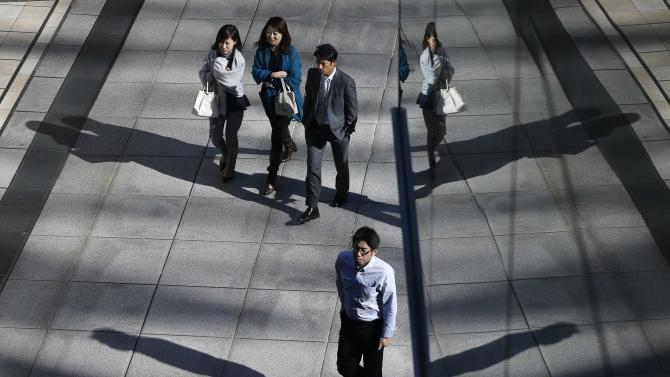 Office workers walk on a street in Tokyo