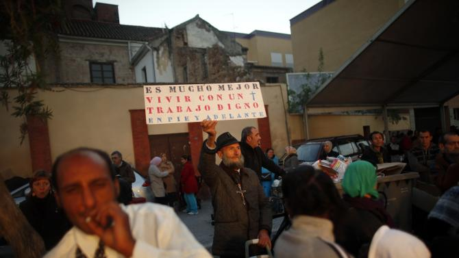 A man holds a sign as he waits to receive food during a daily food distribution organised by Angeles Malaguenos de la noche on Christmas eve on in downtown Malaga