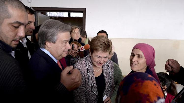 UN High Commissioner for Refugees Antonio Guterres (3rd L) and EU Aid Commisioner Kristalina Georgieva (C) speak with Syrian refugees as they visit the recently opened Vrazhdebna shelter in Sofia on November 22, 2013