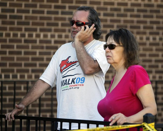 John Priest, left, and Vory Boots watch the police action at an apartment where the suspect in a theatre shooting lived in Aurora, Colo., on Friday, July 20, 2012. The couple were evacuated from their