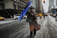 A woman struggles with her umbrella in New York on February 8, 2013 during a storm affecting the northeast US