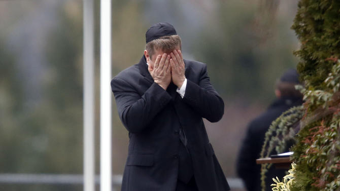 A mourner arrives at the funeral service for 6-year-old Noah Pozner, Monday, Dec. 17, 2012, in Fairfield, Conn. Pozner was killed when a gunman walked into Sandy Hook Elementary School in Newtown Friday and opened fire, killing 26 people, including 20 children. (AP Photo/Jason DeCrow)