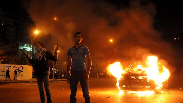 Egyptian protesters pose next to a police vehicle set alight during clashes outside the presidential palace in Cairo, Friday, April 26, 2013. Dozens of mostly masked protesters hurled stones and firebombs in clashes with riot police at Egypt's presidential palace in a Cairo suburb. Protests have become a weekly routine in Egypt, as the country has plunged in turmoil during most of the past two years since 2011 uprising which ousted longtime president Hosni Mubarak out of power. (AP Photo/Hussein Tallal)