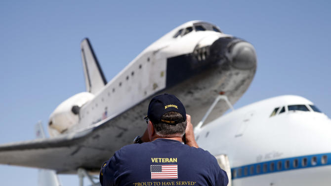 Vietnam war veteran Steve Davis take pictures of the Space Shuttle Endeavour at the NASA Dryden Flight Research Center at Edwards Air Force Base, Calif., Thursday, Sept. 20, 2012. Endeavour returned to its California roots after a wistful cross-country journey that paid homage to NASA workers and former Arizona Rep. Gabrielle Giffords and her astronaut husband. (AP Photo/Jae C. Hong)
