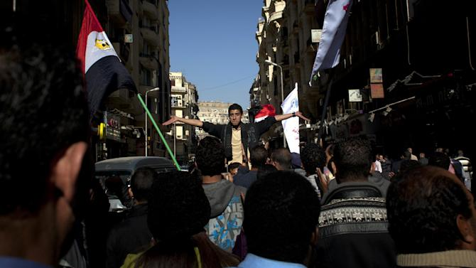 "Egyptian protesters chant slogans denouncing the proposed constitution and the upcoming referendum during a rally in Cairo, Egypt, Thursday, Dec. 13, 2012. Egyptian President Mohammed Morsi's Muslim Brotherhood and other Islamists have been plastering posters across much of the country urging Egyptians to vote ""yes"" and listing what they call the advantages of the new charter. ""Yes, to protecting (Islamic) Sharia (laws),"" says a Brotherhood website. The Islamists have also been using mosques to disseminate the ""yes"" message and putting to use their appeal to uneducated Egyptians in rural areas. But the pros and cons of the draft constitution and the question of whether it will be passed have grown more akin to being a secondary narrative to the worst crisis to hit Egypt since the overthrow nearly two years ago of Hosni Mubarak's authoritarian regime. (AP Photo/Nasser Nasser)"
