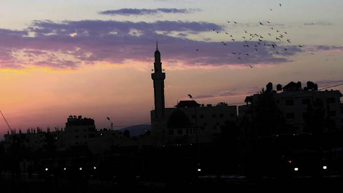 Birds fly over a mosque at the sunrise  in the West Bank refugee camp of Jenin early, Thursday, Oct. 2, 2014. (AP Photo/Mohammed Ballas)